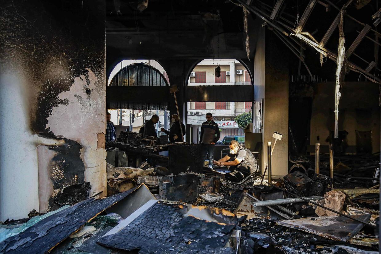 Smeulende resten van een bankgebouw in Tripoli. Voor arme Libanezen horen banken tot de vijandelijke elite. Beeld Ibrahim Chalhoub / AFP