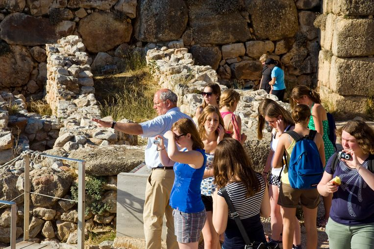 Een leraar met een groep leerlingen op Griekenlandreis, in Mycene, Peloponnesos. Beeld Hollandse Hoogte / Roel Burgler