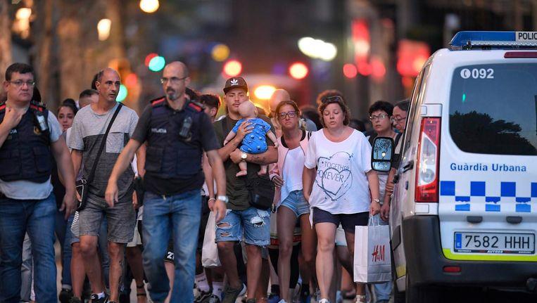 Politie begeleidt klanten een winkel uit. Beeld AFP