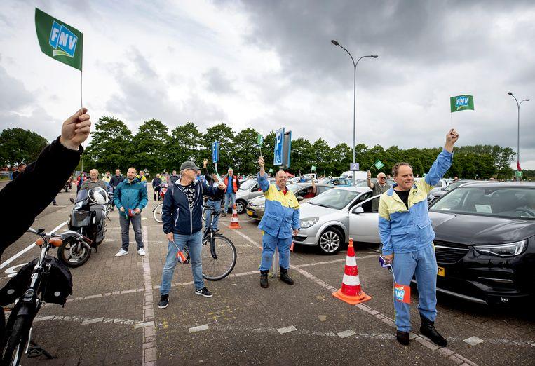 Medewerkers van Tata Steel vorige week tijdens een drive-in-ledenvergadering op de parkeerplaats van De Bazaar in Beverwijk.  Beeld ANP