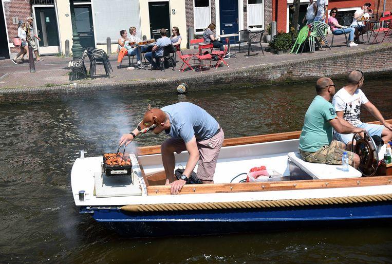 Barbecuen op een bootje door de grachten van Leiden, op een mooie pinksterdag.  Beeld Marcel van den Bergh