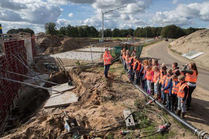 Lutter scholieren nemen een kijkje bij de bouw van een tunnel onder de N34 bij de Pothofweg. Voorlichter Marc Slagter geeft uitleg over het miljoenenproject.