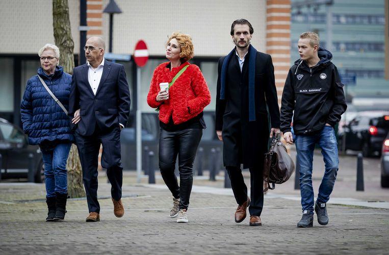 Advocaat Sébas Diekstra (met sjaal) arriveert bij de rechtbank met de vader van een slachtoffer. Foto ANP Beeld EPA