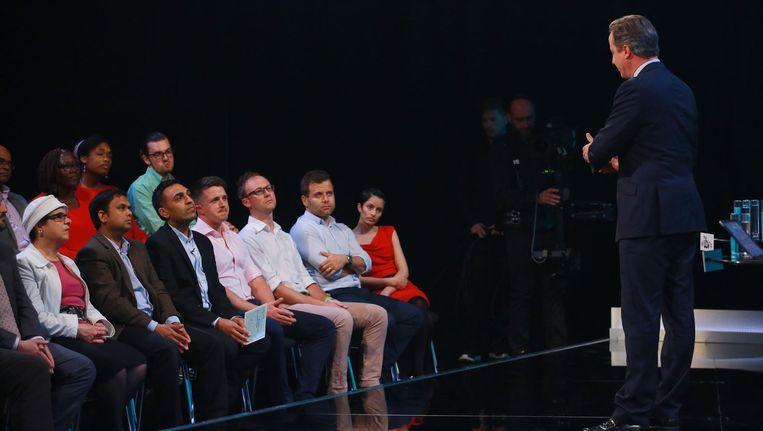 David Cameron praat met kiezers op een televisie-evenement in Londen. De man met het witte papier in zijn hand is Harry Boparai, die door zijn kritische vragen over immigratie, tijdeljke beroemdheid verwierf. Beeld afp