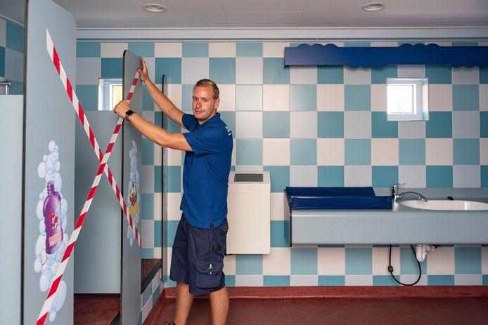 Archieffoto: Miquel Lindeman plakt op camping Julianahoeve in Renesse in toiletgebouwen enkele doucheruimtes af, zodat gasten voldoende afstand van elkaar houden.