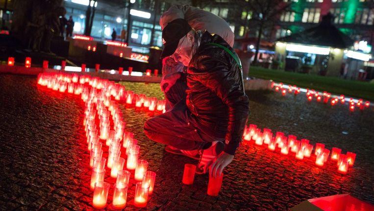 Aan de vooravond van Wereld Aids Dag werden gisteren in Berlijn kaarsen aangestoken die waren neergezet in de vorm van een aidslintje. Beeld epa