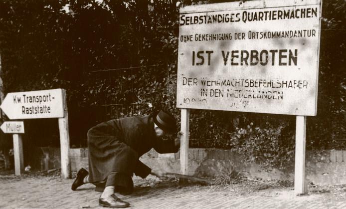 Utrecht, mei 1945. De bevrijding kun je op allerlei manieren vieren. Deze man zaagt in z'n nette jas een bord van de Duitsers om.