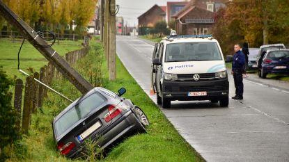 BMW slipt en knalt in gracht tegen elektriciteitspaal