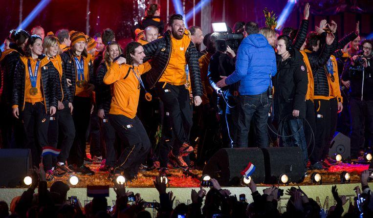 Schaatser Bob de Jong (L) en snowboarder Dolf van der Wal tijdens de huldiging van het olympisch team op een podium in de binnenstad van Assen. Beeld anp