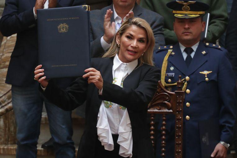 Interim-president Jeanine Anez met de noodwet die nieuwe verkiezingen in Bolivia mogelijk maakt. Beeld EPA
