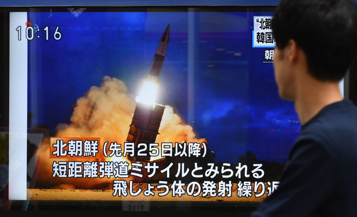 Een voetganger in Tokio kijkt op straat naar een tv-uitzending waarin bericht wordt over de laatste raketlancering van Noord-Korea.