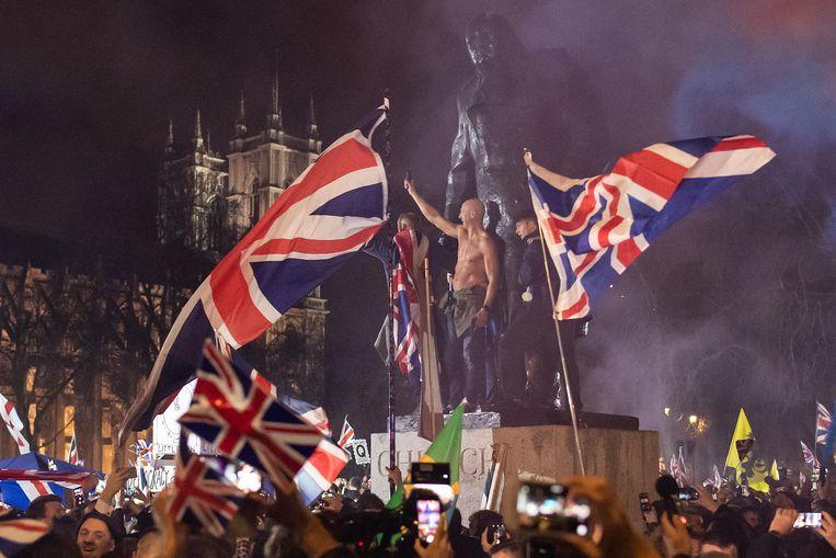 Winston Churchill krijgt op zijn sokkel gezelschap van enkele jongemannen in ontblote bovenlijven.  Beeld Getty Images