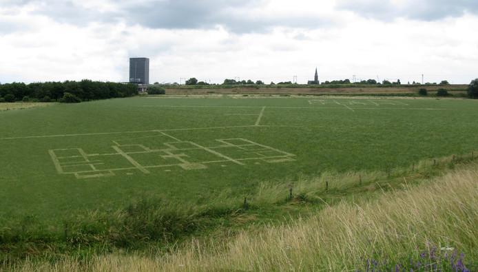Een tekening in het grasveld simuleert een plattegrond van een gebouw. Het kunstwerk blikt vooruit, oogt als een opgraving over 100 jaar.