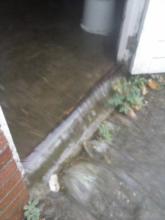 Het water stroom er aan de achterkant van de garage weer uit.  Eigen foto
