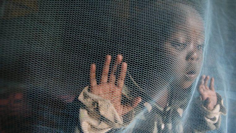 Een Keniaans jongetje speelt achter een muskietennet dat hem moet beschermen tegen malaria muggen. Foto ANP Beeld