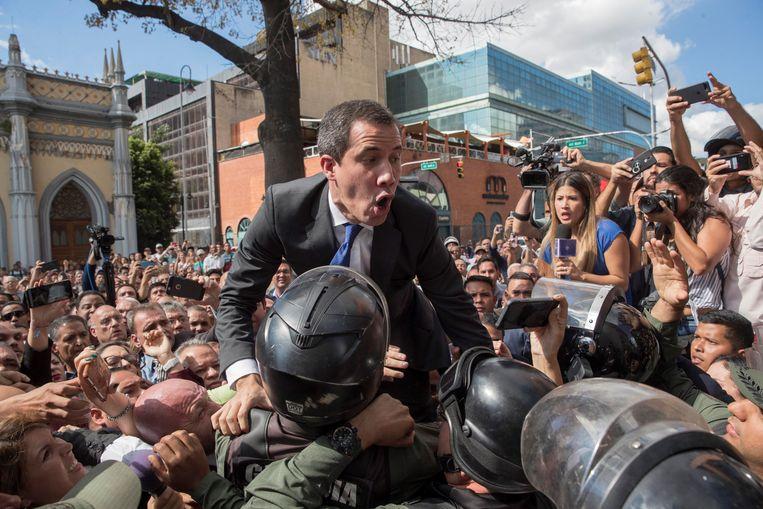 Venezolaanse ordetroepen proberen oppositieleider Juan Guaidó tegen te houden als hij dinsdag het parlementsgebouw in Caracas probeert binnen te komen. De politie moest uiteindelijk wijken, waarna de parlementariërs Guaidó opnieuw aanwezen als parlementsvoorzitter en interim-president. Beeld null