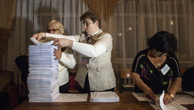 Leden van een kiescommissie tellen de stemmen na sluiting van een stembureau in Donetsk. Beeld ap