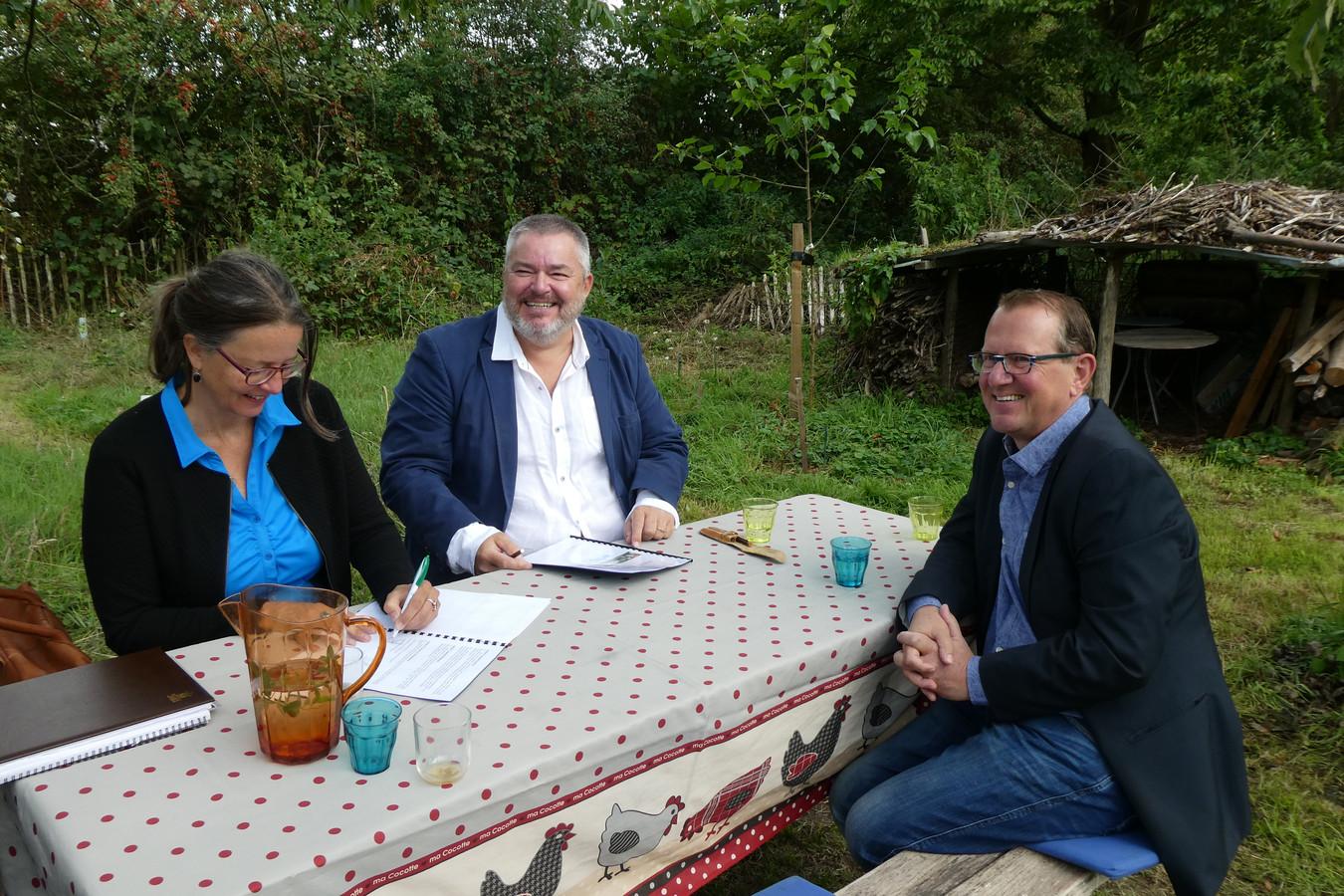 Patricia van Rooij en Rik Spooren ondertekenen de intentieovereenkomst zodat Erbij Dagebesting aan de slag kan bij De Kleine Aarde. Guido van de Laar, een van de eigenaren van Erbij Dagbesteding, kijkt toe.