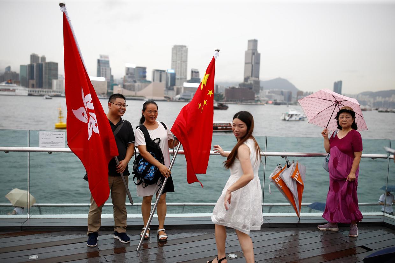 Mensen poseren met de vlaggen van China en Hongkong om hun steun voor de politie in Hongkong te laten zien.