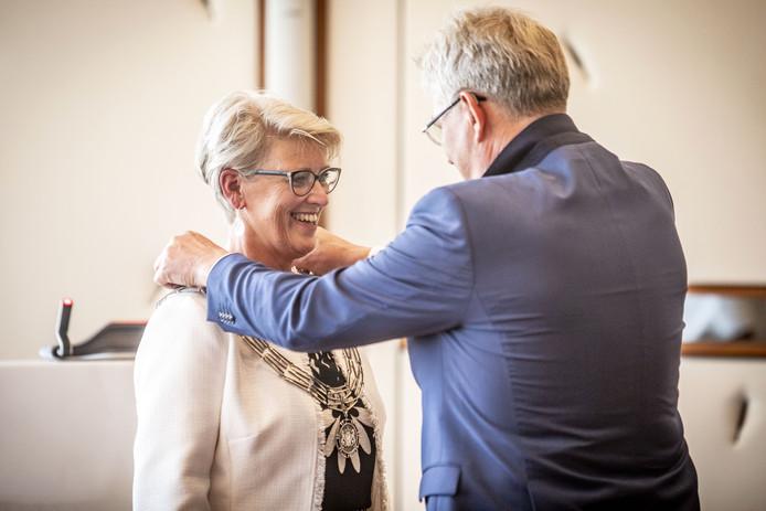Loco-burgemeester Johan Coes hangt de ambtsketen om bij Doret Tigchelaar.