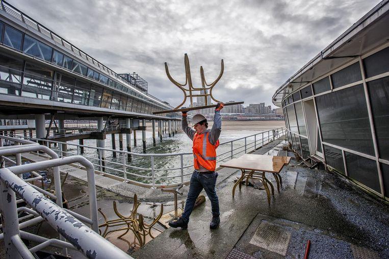 Een man verwijdert oude tafels uit het restaurant van de Pier van Scheveningen Beeld Raymond Rutting