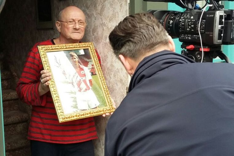 Een buurtbewoner van Cruijfs geboorteplek in Betondorp toont een foto van de legendarische nummer 14 aan de pers. Beeld Hanneloes Pen