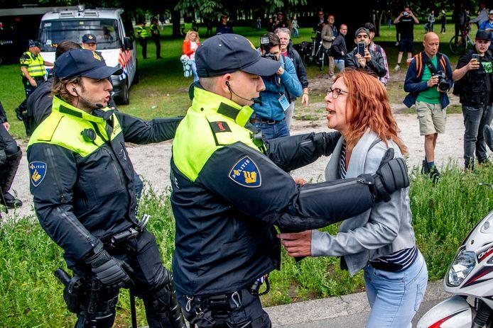 Een demonstrant vaart uit tegen de politie, die mensen wegstuurt omdat de demonstratie verboden was.