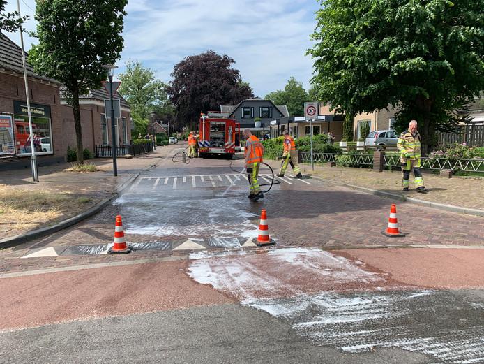 Brandweerlieden en medewerkers van de gemeente ruimen de olie op straten in Bathmen op.