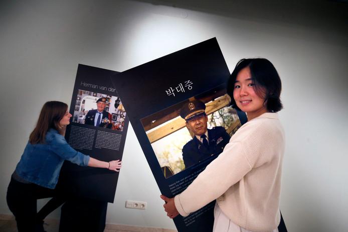 Jihyun Park met het paneel waarop haar opa staat. Marissa Wouda houdt dat van veteraan Herman van der Leelie vast.