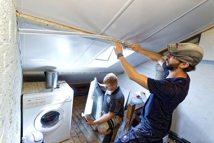 Twee vakmannen installeren isolatieplaten in een woning.