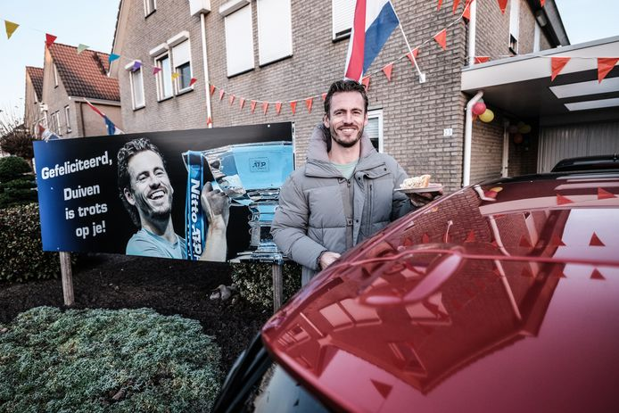 Wesley Koolhof poseert voor het bord dat de buurtgenoten in de tuin hebben  geplaatst.