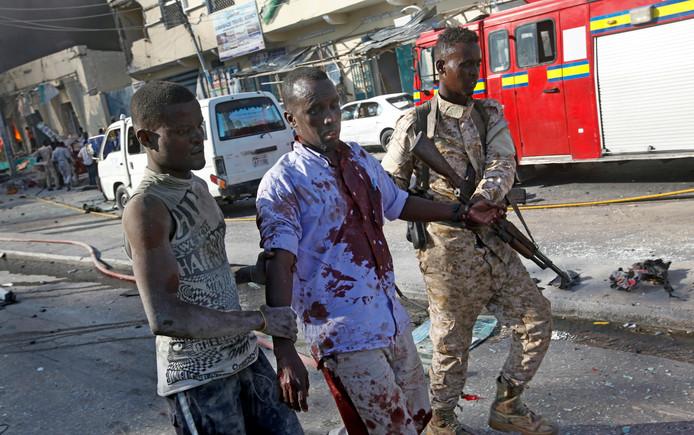 Een soldaat en een voorbijganger helpen een gewonde man na de dubbele aanslag in de Somalische hoofdstad Mogadishu.