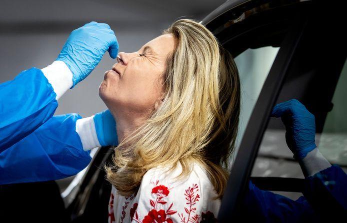 Een medewerker van de GGD neemt een coronatest af in een teststraat.