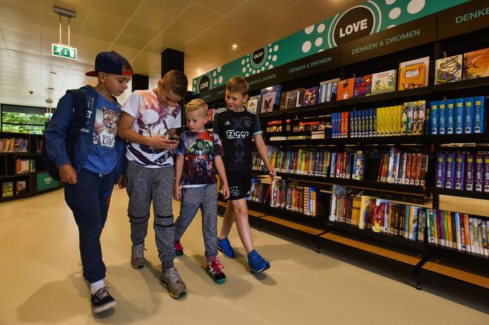 Kinderen zoeken in de bibliotheek in Waalwijk naar Pokémon.