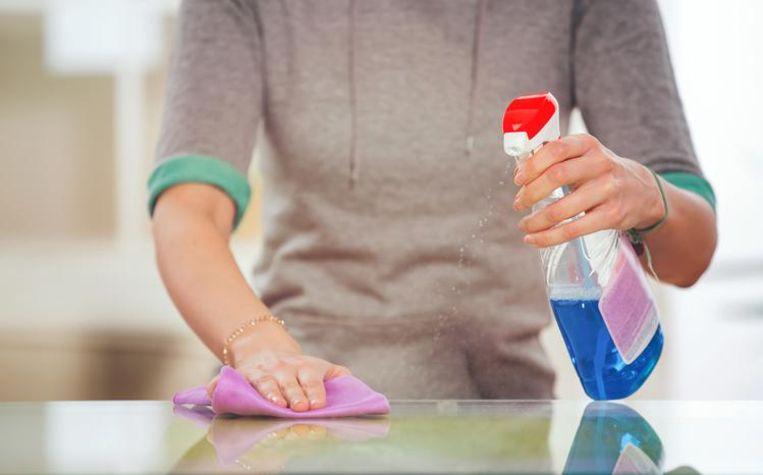 Een vrouw maakt een tafel schoon.