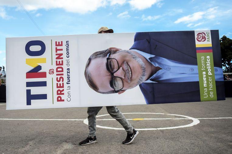 Een man loopt met het portret van Farc-presidentskandidaat Rodrigo Londono over straat in de Colombiaanse hoofdstad Bogota, eind januari. Londono heeft zich inmiddels teruggetrokken. Beeld AFP