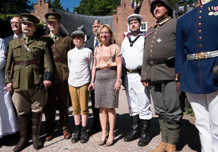 Minister Jet Bussemaker (midden) omringd door living historyspelers voor het poortgebouw van Huis Doorn. Bussemaker heropende het monument na een grondige renovatie.