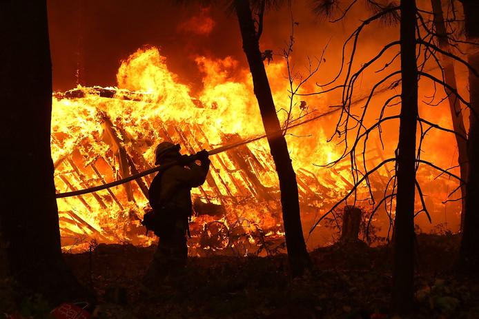 Brandweerlieden proberen een woning in Magalia, Californië, te behoeden voor de vlammen
