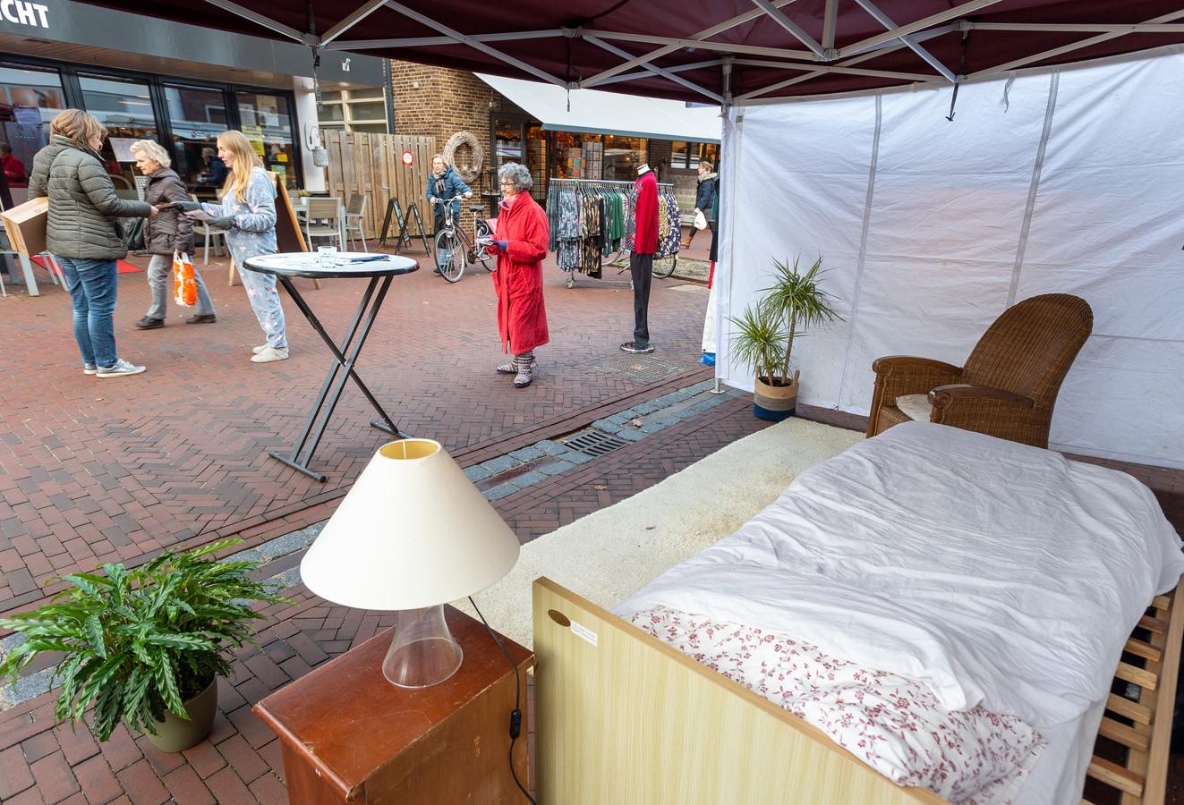 Esmee de With en Astrid de la Fuente (met rode badjas) staan in pyjama op de markt in Vaassen om aandacht te vragen voor logeerzorg.