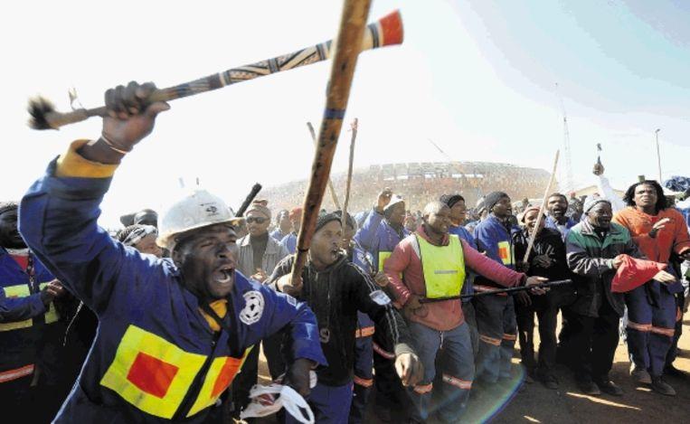 Gewapend met stokken uiten stakende arbeiders hun woede. ( FOTO AFP) Beeld