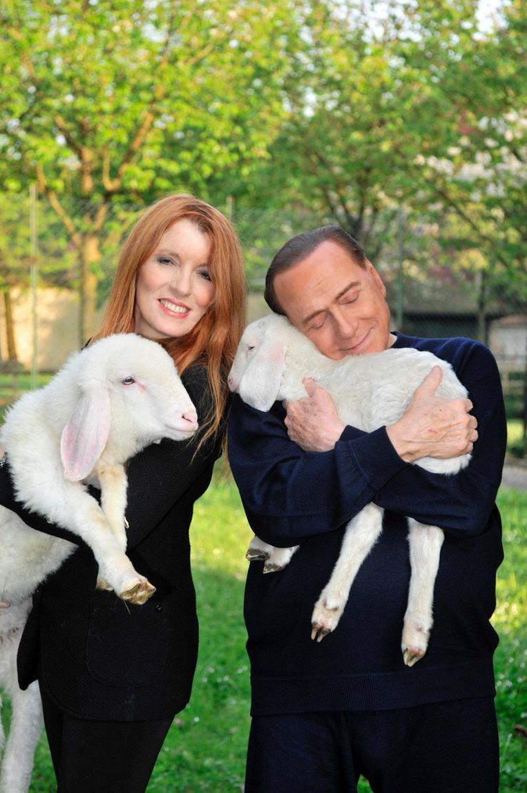 Michela Vittoria Brambilla, dierenrechtenactivist en Forza Italia-politicus, knuffelt lammetjes met Silvio Berlusconi, die in 2016 vegetariër werd. Beeld reuters