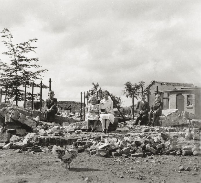 LEUSDEN, 14 JULI 1940 De kinderen van de familie Van Eijden — Johan, Marietje, Annie, René en Jan — poseren voor de foto op de ruïnes van wat voorheen hun ouderlijk huis was. Tijdens de strijd om de Grebbelinie in mei 1940 is ook hun boerderij uit 1926 verwoest. René van Eijden, helemaal rechts, herinnert zich het moment van de foto nog heel goed: ,,We werden geëvacueerd naar het dorpje De Rip in Noord-Holland. Toen we terugkwamen naar onze boerderij zagen we de ruïne. Er was bijna niks van over. De woning, de schuur, alles was plat.'' Terwijl de familie onderdak vond in een barak, werd de boerderij in 1941 herbouwd. In de laatste week van april 1945 werd de boerderij opnieuw in brand gestoken. Uiteindelijk is de boerderij voor de tweede keer herbouwd en is deze nog altijd in bezit van de familie. ,,Het is nu een goedlopend agrarisch bedrijf. Dat is een overwinning. Maar de echte overwinning is dat we de oorlog overleefd hebben'', aldus Van Eijden.