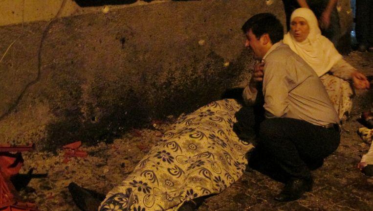 Nabestaanden bij het lichaam van een slachtoffer van de aanslag. Beeld reuters