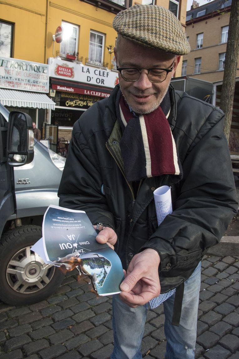 Etienne Wattecamps verbrandt één van de folders die Els Ampe uitdeelde. Op 8 december geeft de schepen een infovergadering voor bewoners en handelaars van het Vossenplein.