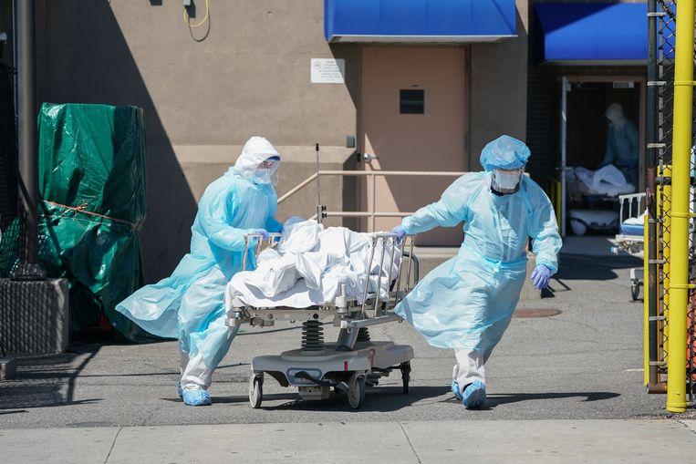Bij het Wyckoff Hospital in Brooklyn worden lichamen verplaatst naar koeltrucks, die als tijdelijke mortuaria fungeren. Beeld AFP