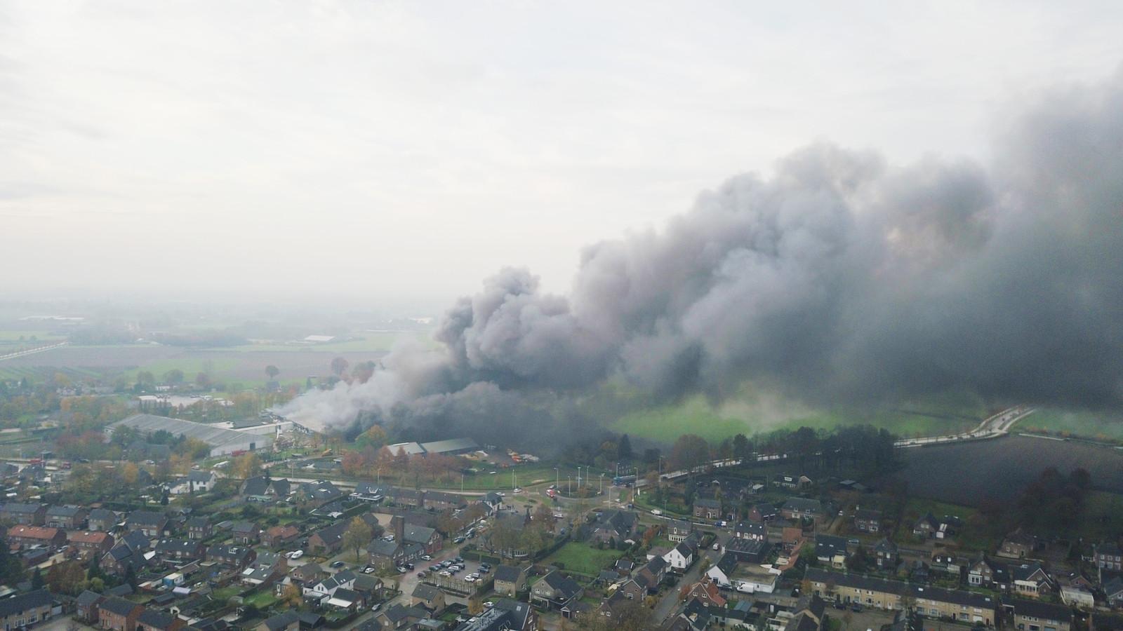 Een grote rookpluim stijgt op van Caravanstalling Oeffelt.