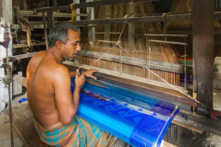 In weversdorp Bishnupur zijn de rollen duidelijk verdeeld: de mannen weven, de vrouwen knippen. Beeld null