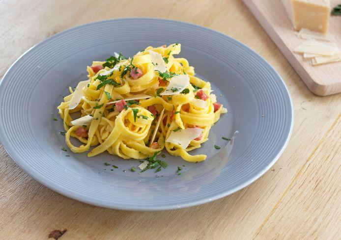 Pasta carbonara met spekblokjes en peterselie.