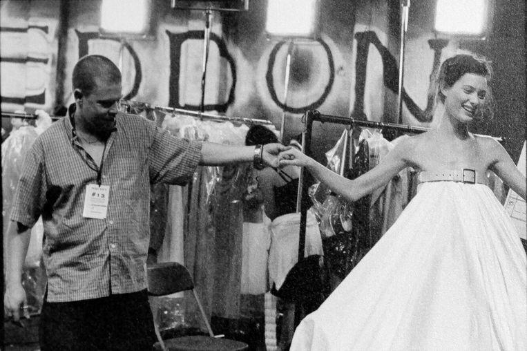 Alexander McQueen houdt de hand vast van een model in een van zijn shows.