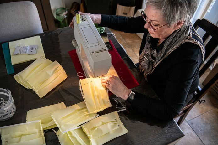 Jeanne van Ooijen is bezig met het maken van mondkapjes